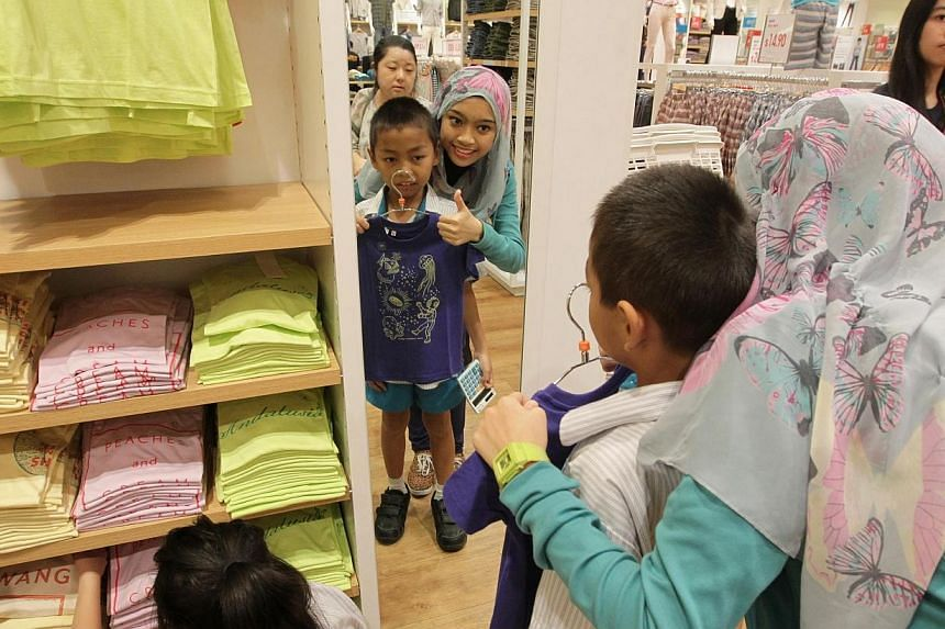 Uniqlo takes 24 special needs students from MINDS and 4 adults with intellectual disabilities for a shopping trip as part of its ongoing CSR efforts at its outlet in Suntec City on Mar 27, 2014. -- ST PHOTO: NEO XIAOBIN