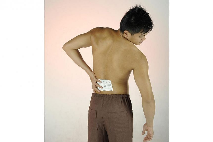 Posed photo of a man with a medicated plaster pasted on his back.Stiff necks from bad posture at work, strained backs from lifting boxes and numb wrists from too much typing - these and other ergonomic health issues cost Singapore a whopping $3