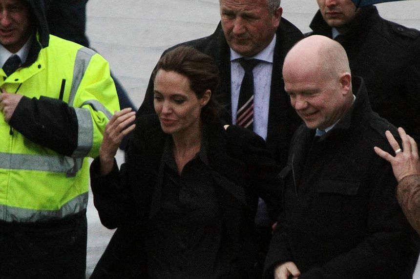 Hollywood superstar Angelina Jolie (second from left) and British Foreign Secretary (right) are welcomed upon arrival at Sarajevo International Airport late on March 27, 2014. Jolie arrived in Sarajevo on Thursday with Hague to take part in a confere