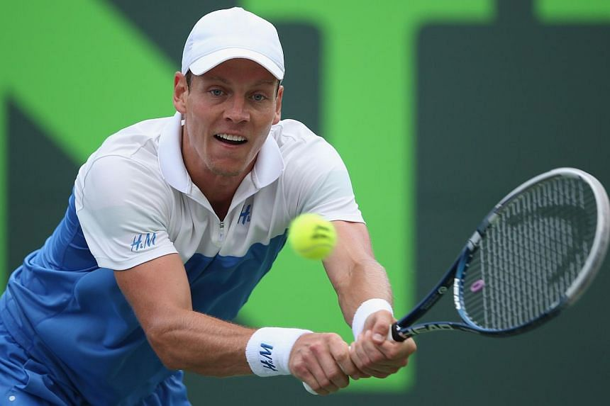 Tomas Berdych of the Czech Republic plays a backhand against Alexandr Dolgopolov of the Ukraine during their quarter-final match on day 11 at the Sony Open at Crandon Park Tennis Centre on March 27, 2014, in Key Biscayne, Florida. -- PHOTO: AFP