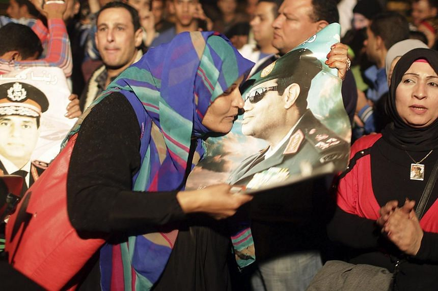 A woman kisses a poster of Egypt's army chief Field Marshal Abdel Fattah al-Sisi as people celebrate after Mr Sisi declared his candidacy for a presidential election, at Tahrir Square in Cairo on March 26, 2014. -- FILE PHOTO: REUTERS