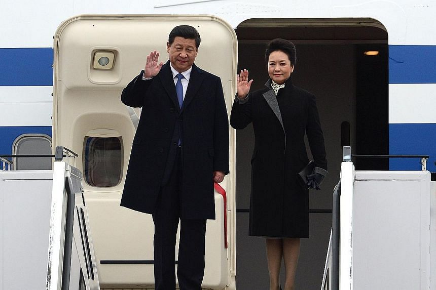 Chinese President Xi Jinping and his wife Peng Liyuan wave upon arrival at Berlin Tegel airport on March 28, 2014. -- PHOTO: AFP