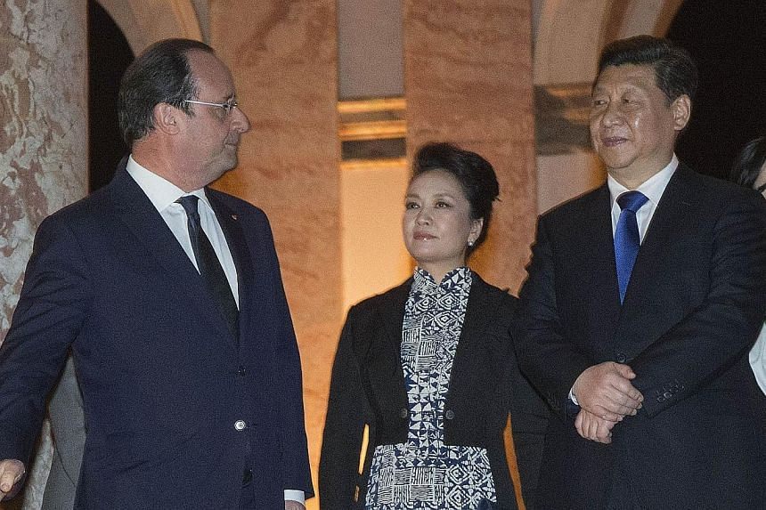 French President Francois Hollande (left), Chinese President Xi Jinping (right) and Xi Jinping's wife Peng Liyuan arrive at the Grand Trianon of the Chateau de Versailles for a dinner in Versailles, outside Paris, on March 27, 2014. -- PHOTO: AFP