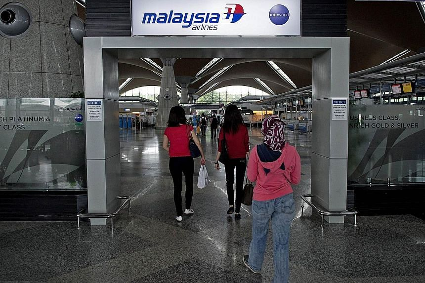 Passengers walk under the Malaysia Airlines logo at Kuala Lumpur International Airport (KLIA) in Sepang, outside Kuala Lumpur on March 16, 2014. Several top online travel agencies in China have announced a boycott of Malaysia Airlines (MAS) unti