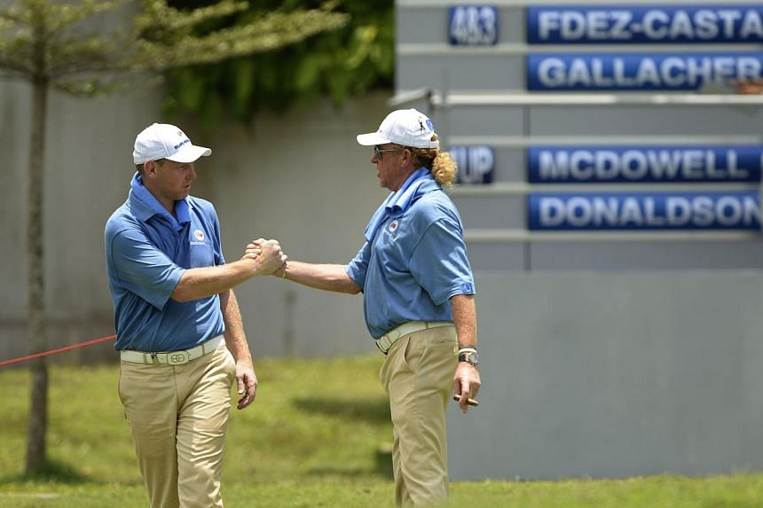 Stepehn Gallacher of Scotland (left) being congratulated by captain Miguel Angel Jimenez of Spain during the EurAsia Cup in Glenamarie Golf and Country Club in Kuala Lumpur, on March 26, 2014. Europe remain in pole position going into the final round