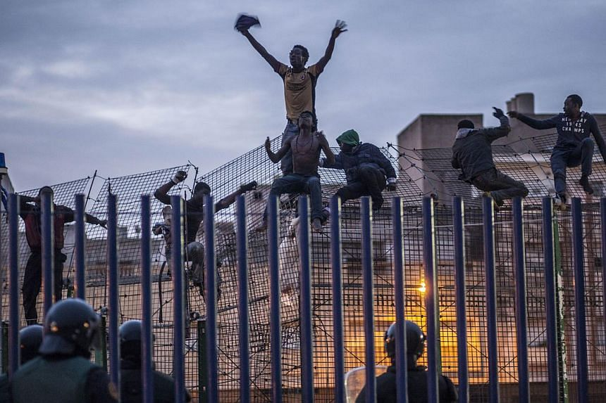 Spanish policemen watch would-be immigrants reacting on a fence near Beni Enza, into the north African Spanish enclave of Melilla on March 28, 2014. -- PHOTO: AFP