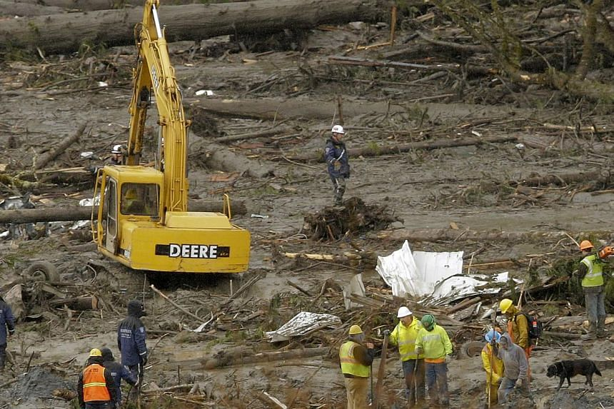 An excavator is used as search work continues in the mud and debris from a massive mudslide that struck Oso near Darrington, Washington, on March 27, 2014. Washington state officials said the confirmed death toll from a huge mudslide in the US Pacifi