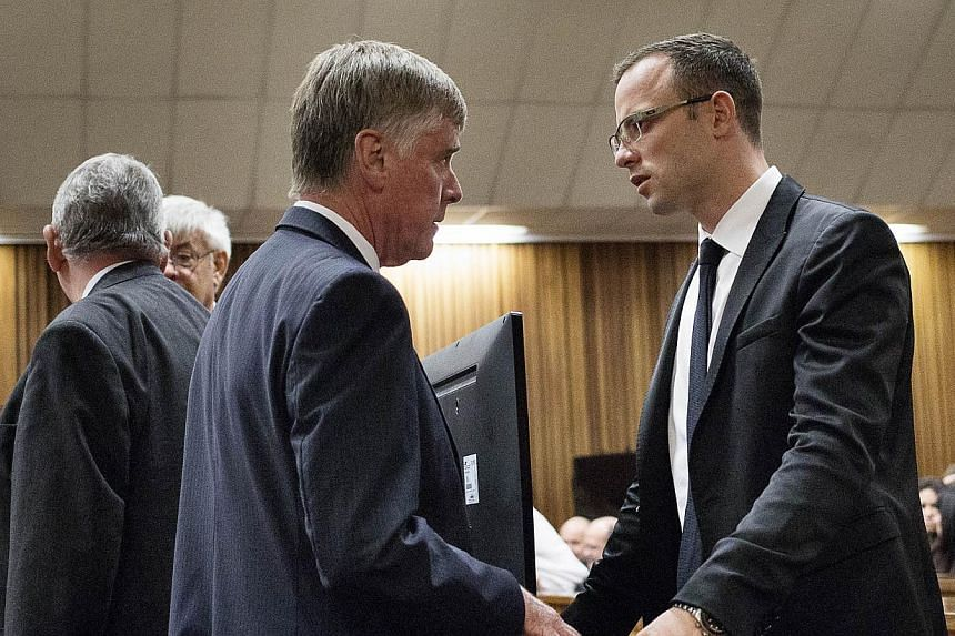 Olympic and Paralympic track star Oscar Pistorius consults with members of his legal team at the North Gauteng High Court in Pretoria, on March 28, 2014. The murder trail of Oscar Pistorius was adjourned on Friday until April 7, when the South Africa