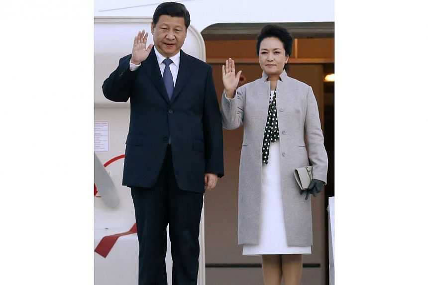 China's President Xi Jinping (left) and his wife Peng Liyuan wave as they arrive at the Lyon-Saint-Exupery airport in Colombier-Saugnieu, near Lyon, on March 25, 2014. -- FILE PHOTO: REUTERS