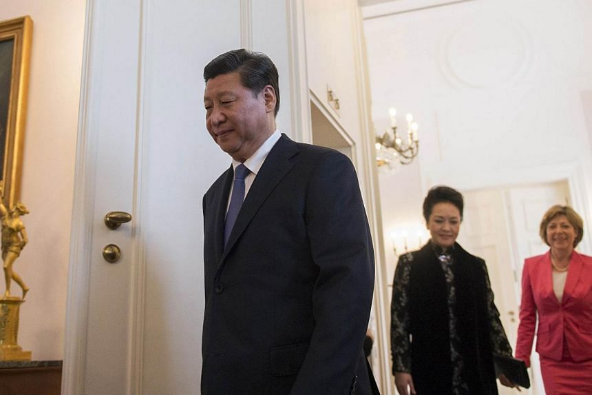 Chinese President Xi Jinping (left) is followed by wife Peng Liyuan (second right) and Geman president's companion Daniela Schadt during his visit at the Schloss Bellevue presidential residency in Berlin, on March 28, 2014. -- PHOTO: AFP