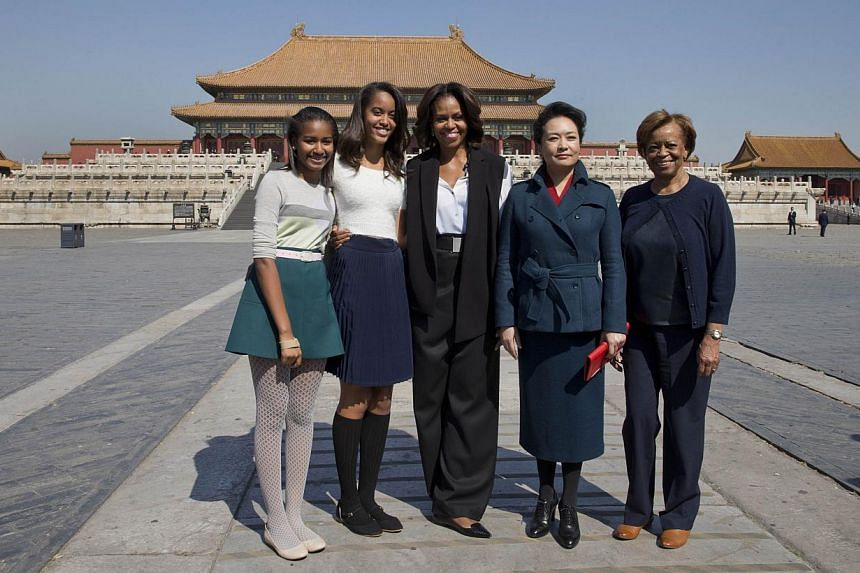 US First Lady Michelle Obama (centre), her daughters from Sasha (left), Malia (second from left), her mother Marian Robinson (right) and Peng Liyuan, wife of Chinese President Xi Jinping pose for photographers as they visit the Forbidden City in Beij