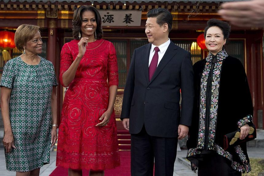 US first lady Michelle Obama, her mother Marian Robinson (left), share a light moment with Chinese President Xi Jinping, and his wife Peng Liyuan (right) after a photograph session at the Diaoyutai State guest house in Beijing, on March 21, 2014. --