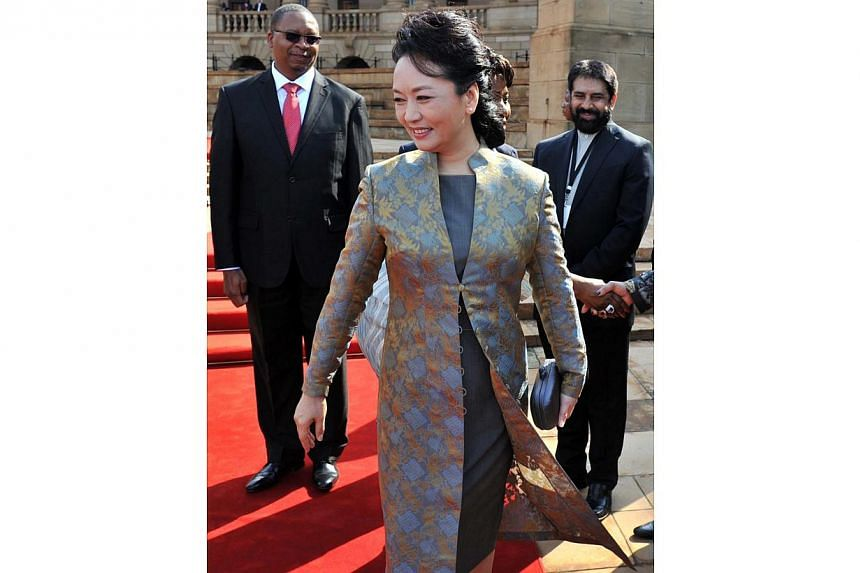 Peng Liyuan, the wife of Chinese President Xi Jinping (centre), is welcomed by officials upon arrival in Pretoria for a state visit, on March 26, 2013. -- FILE PHOTO: AFP