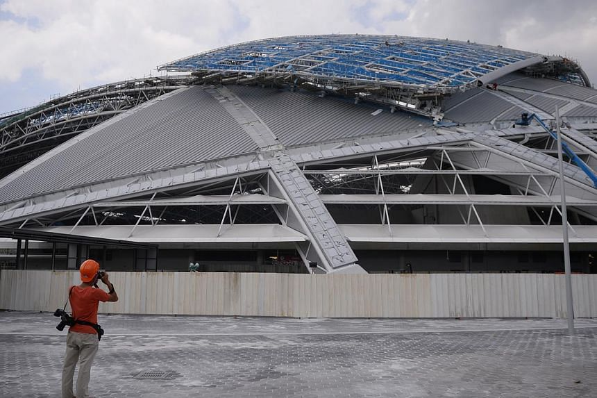 A press photographer takes a photo of the exterior of the stadium at the Singapore Sports Hub pictured on March 27, 2014. -- PHOTO: MARK CHEONG