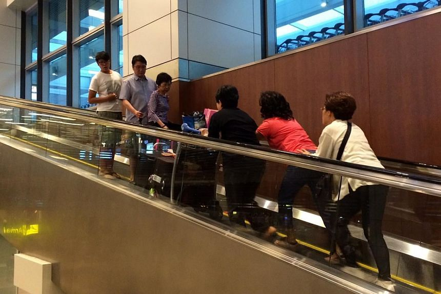 Confusion on stationary travellers, people have to push heavy luggage trolleys up. -- ST PHOTO: SHEA JOHN DRISCOLL