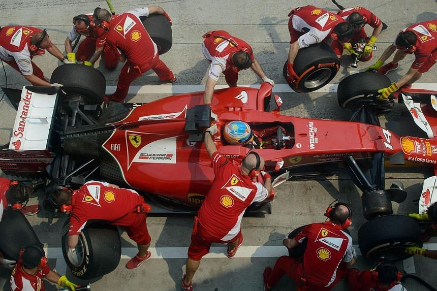 Ferrari driver Fernando Alonso of Spain enters the pit during the second practice session of the Formula One Malaysian Grand Prix at the Sepang circuit near Kuala Lumpur on March 28, 2014. -- PHOTO: AFP