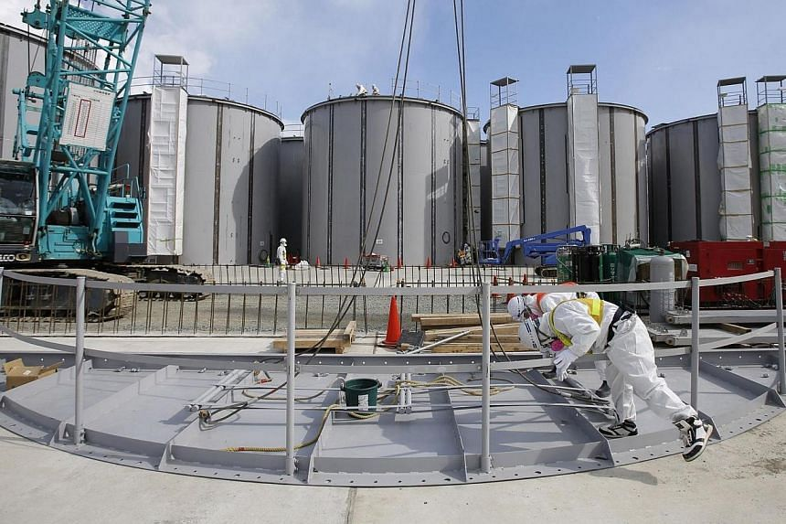 Men wearing protective suits and masks work in front of welding storage tanks for radioactive water, under construction in the J1 area at the Tokyo Electric Power Co's (Tepco) tsunami-crippled Fukushima Daiichi nuclear power plant in Okuma in Fukushi