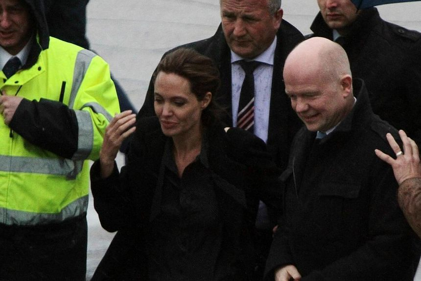 Hollywood superstar Angelina Jolie (second left) and British Foreign Secretary (right) are welcomed upon arrival at Sarajevo International Airport late on March 27, 2014.Hollywood superstar Angelina Jolie and British Foreign Minister William Ha