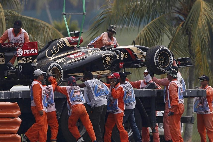 The car of Lotus Formula One driver Romain Grosjean of France is removed from the tracks during the second practice session of the Malaysian F1 Grand Prix at Sepang International Circuit outside Kuala Lumpur on March 28, 2014. -- PHOTO: REUTERS