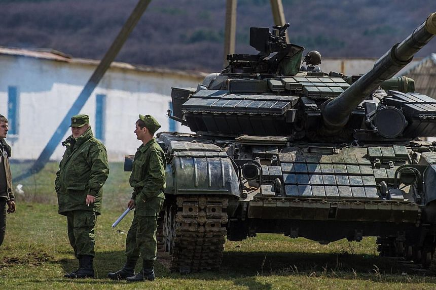 Russian soldiers stand near a tank outside a former Ukrainian military base in Perevalnoye, near the Crimean capital Simferopol on March 27, 2014. -- PHOTO: AFP