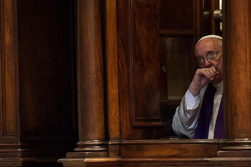 Pope Francis listens to a confession during a Penitential Liturgy ceremony in St. Peter's Basilica at the Vatican on March 28, 2014. -- PHOTO: REUTERS