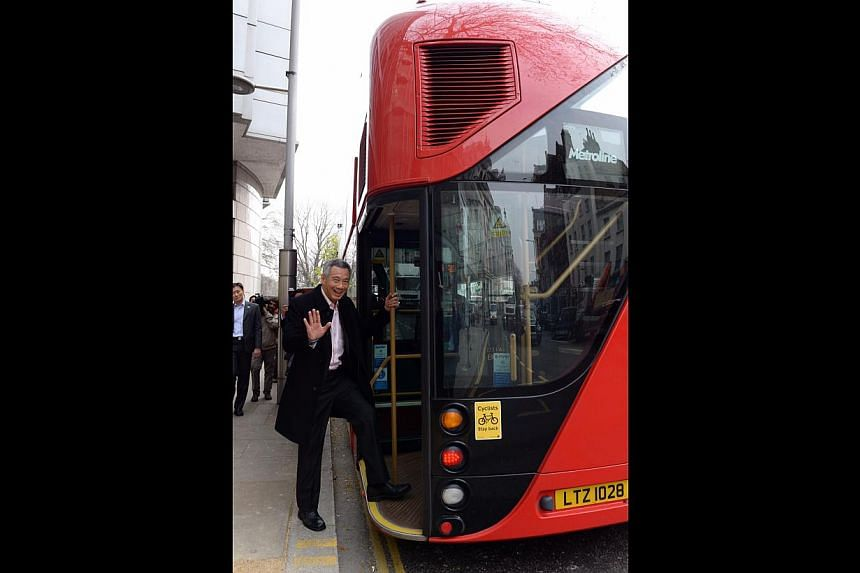 PM Lee boarding a Routemaster bus (above) in London yesterday and holding up the Freedom of the City award presented to him during a ceremony on Thursday by Lord Mayor Fiona Woolf. Mr Lee also took part in a dialogue on ''Singapore's Perspectiv