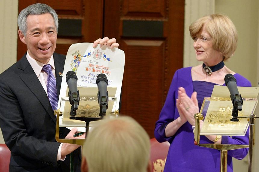 PM Lee boarding a Routemaster bus in London yesterday and (above) holding up the Freedom of the City award presented to him during a ceremony on Thursday by Lord Mayor Fiona Woolf. Mr Lee also took part in a dialogue on ''Singapore's Perspectives on