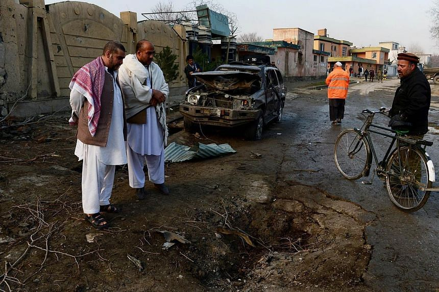 Afghan men look at a crater from a car bomb detonated outside the guesthouse which was attacked by Taleban militants the previous night, on March 29, 2014. Taleban insurgents attacked the Afghan election commission's heavily-fortified headquarters in