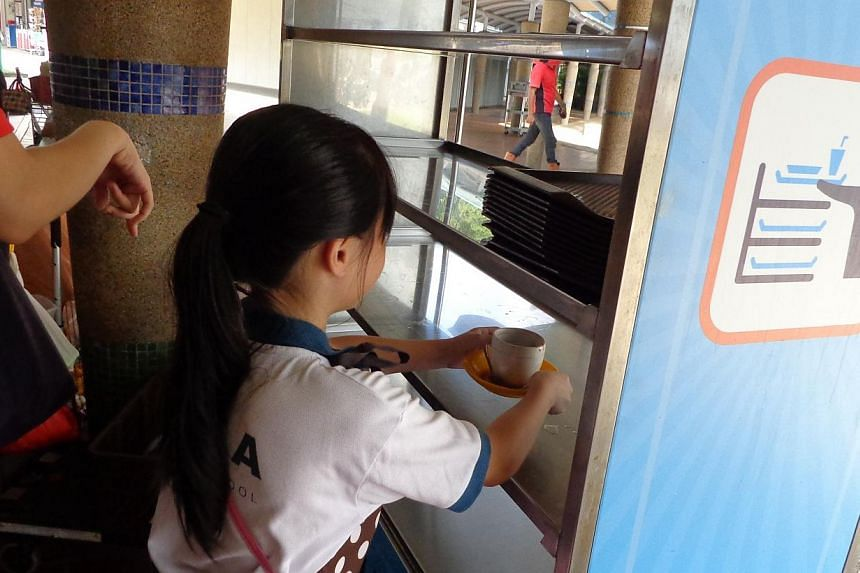 Nearly 40 primary school students paired up with grassroots volunteers to promote a tray return campaign at Ayer Rajah hawker centre on Saturday morning. -- PHOTO:WEST COAST CONSTITUENCY OFFICE