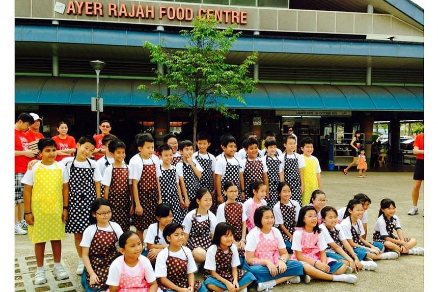 Nearly 40 primary school students paired up with grassroots volunteers to promote a tray return campaign at Ayer Rajah hawker centre on Saturday morning. -- PHOTO: WEST COAST CONSTITUENCY OFFICE
