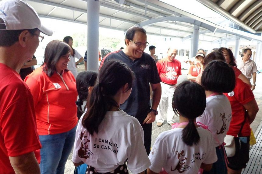 West Coast GRC MP and Second Minister for Home Affairs and Trade and Industry S Iswaran, (centre) with a student at Ayer Rajah hawker centre on Saturday morning. -- PHOTO: WEST COAST CONSTITUENCY OFFICE