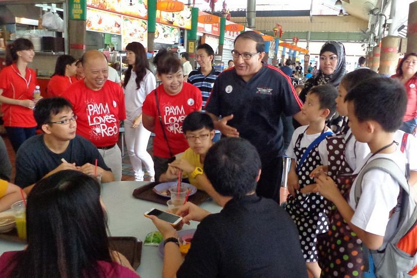 West Coast GRC MP and Second Minister for Home Affairs and Trade and Industry S Iswaran, (centre) witha student at Ayer Rajah hawker centre on Saturday morning. -- PHOTO:WEST COAST CONSTITUENCY OFFICE