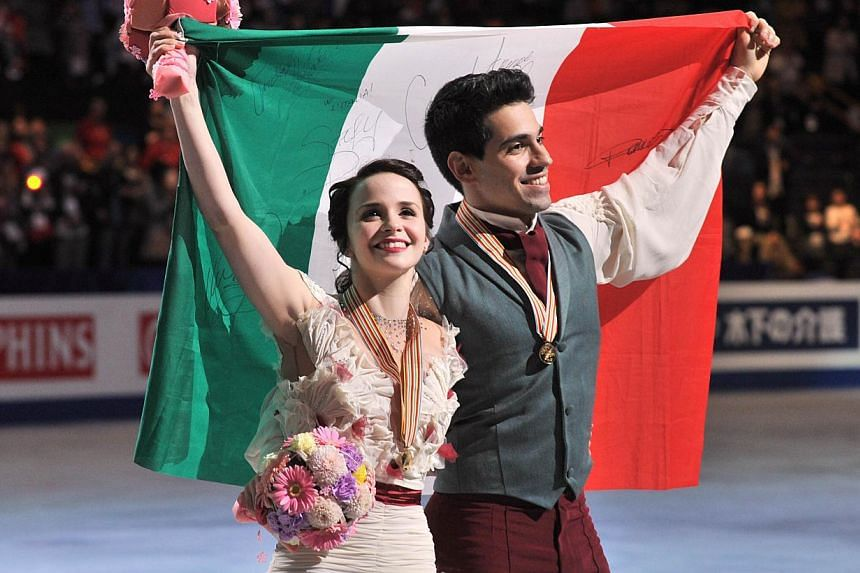Italy's Anna Cappellini and Luca Lanotte celebrate their victory during the award ceremony of the ice dance free dance competition at the world figure skating championships in Saitama, on March 29, 2014. Cappellini and Lanotte of Italy won the i