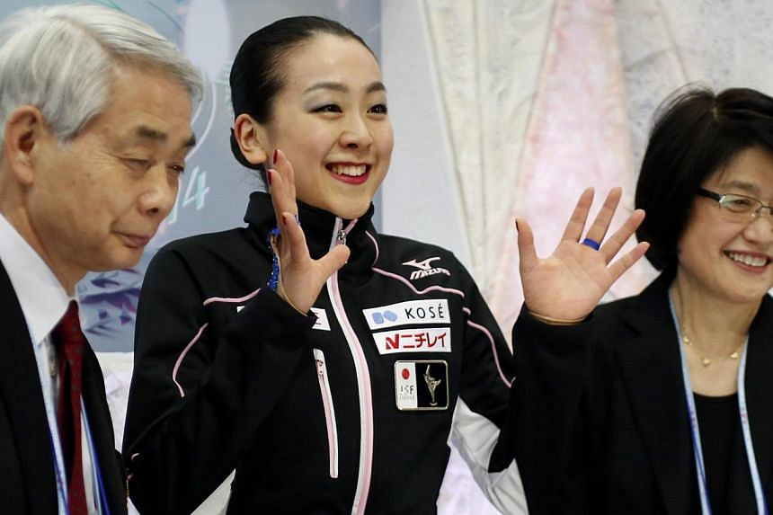 "Japan's Mao Asada (centre) reacts at the ""kiss and cry"" area after the women's free program at the ISU World Figure Skating Championships in Saitama, north of Tokyo, on March 29, 2014. Asada won her third women's world championship title Saturday, pu"