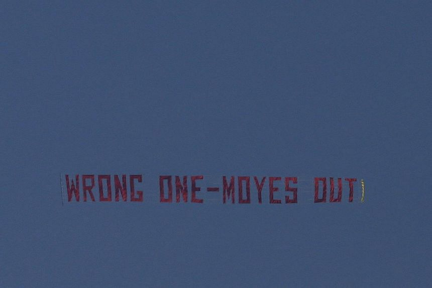 A plane flies a banner over Old Trafford ahead of the English Premier League soccer match between Manchester United and Aston Villa in Manchester, northern England, on March 29, 2014. A plane trailing a banner calling for the dismissal of beleaguered