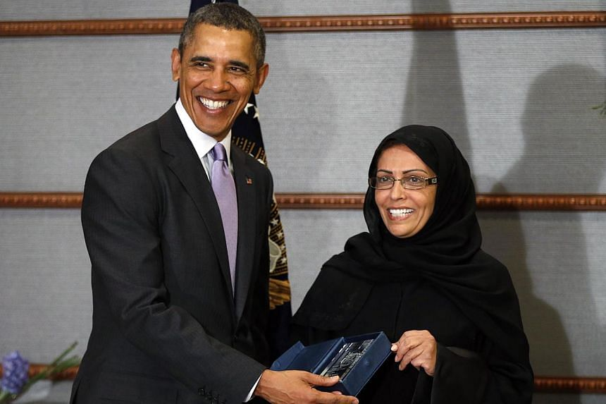 US President Barack Obama (left) presents the executive director of Saudi Arabia's National Family Safety Program Maha Al Muneef with the US Secretary of State's International Woman of Courage Award in Riyadh, on March 29, 2014. -- PHOTO: REUTERS
