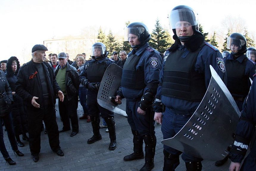 Pro-Russian activists (left) speak to police officers guarding the regional state administration building in the eastern Ukrainian city of Donetsk during a rally on March 22, 2014. -- FILE PHOTO: AFP