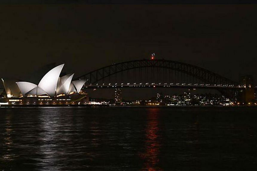 The Sydney Harbour Bridge is seen plunged into darkness for the Earth Hour environmental campaign, among the first landmarks around the world to dim their lights for the event, on March 29, 2014. -- PHOTO: AFP
