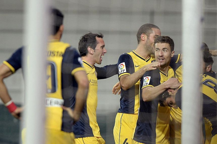 Atletico Madrid players celebrating a goal against Athletic Bilbao during their Spanish first division match at San Mames stadium in Bilbao on March 29, 2014. -- PHOTO: REUTERS