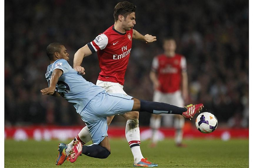 Manchester City's Brazilian midfielder Fernandinho (left) vies with Arsenal's French striker Olivier Giroud during the English Premier League football match between Arsenal and Manchester City at the Emirates Stadium in London on March 29, 2014. -- P