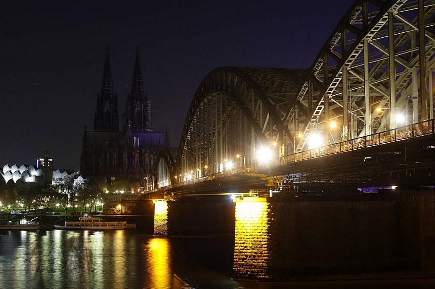 The UNESCO World Heritage Cologne Cathedral and the Hohenzollern railway bridge along the river Rhine are seen during Earth Hour on March 29, 2014. -- PHOTO: REUTERS
