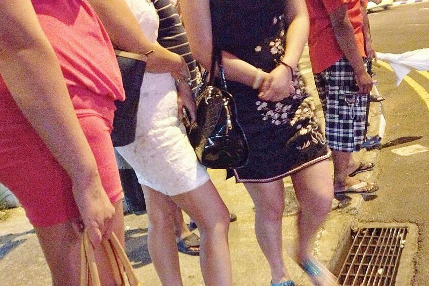 (Above) Streetwalkers standing along the junction of Geylang Road and Geylang Lorong 22 last Thursday. Donning skimpy outfits, they emerge at dusk like clockwork and flirt with men, both foreign and local. -- ST PHOTOS: DESMOND WEE