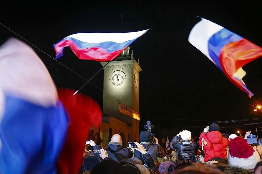 People celebrate the ceremonial change of time on the railway square in the Crimean city of Simferopol on March 30, 2014. -- PHOTO: REUTERS