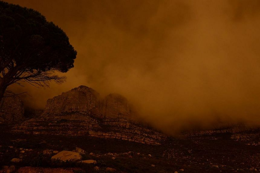 Table Mountain is plunged into darkness for the global Earth Hour initiative in Cape Town on March 29, 2014. -- PHOTO: AFP