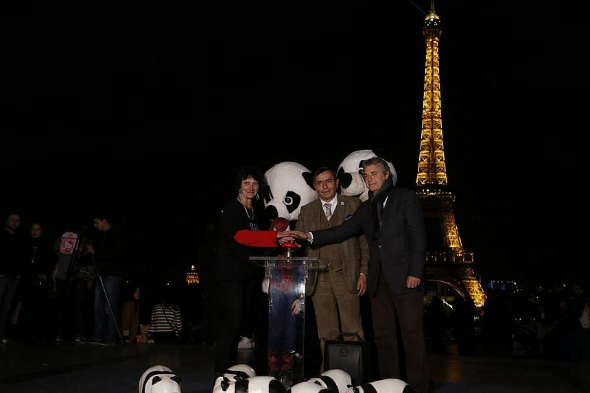 People dressed as pandas and as Spider-man, president of World Wide Fund for Nature (WWF) for France Isabelle Autissier (left), director-general of WWF for France Philippe Germa (second right), and Sony Pictures Releasing France director-general Eric