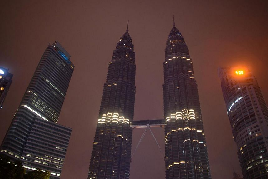 A general view shows the Petronas towers in Kuala Lumpur after the lights of have been switched off for earth hour on March 29, 2014. -- PHOTO: AFP