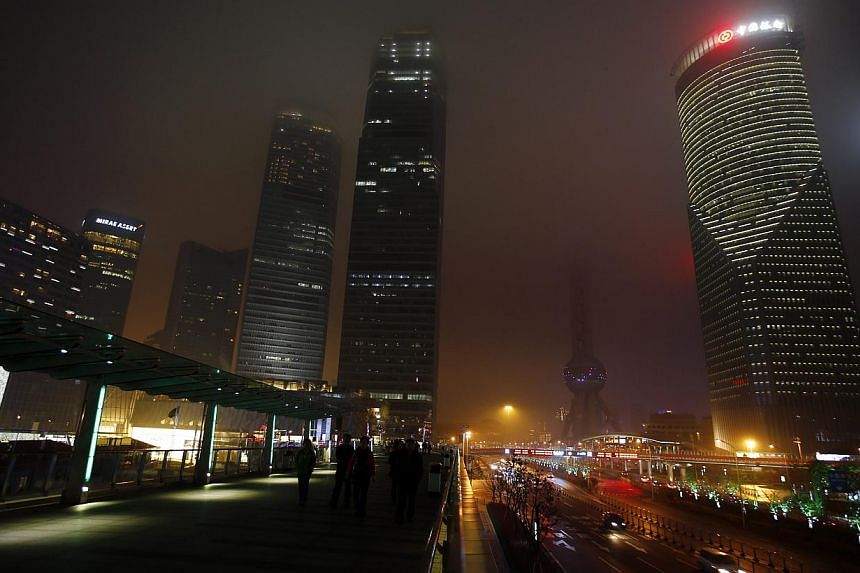 People walk at the financial district of Pudong during Earth Hour in Shanghai on March 29, 2014. -- PHOTO: REUTERS