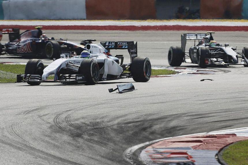 Williams Formula One driver Felipe Massa of Brazil passes debris on the track during the Malaysian F1 Grand Prix at Sepang International Circuit outside Kuala Lumpur, on March 30, 2014. -- PHOTO: AFP