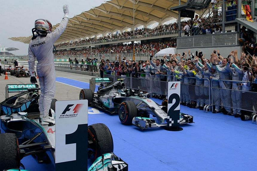 Mercedes driver Lewis Hamilton of Britain (left) waves from his car after winning the Formula One Malaysian Grand Prix at the Sepang circuit near Kuala Lumpur on March 30, 2014. -- PHOTO: AFP