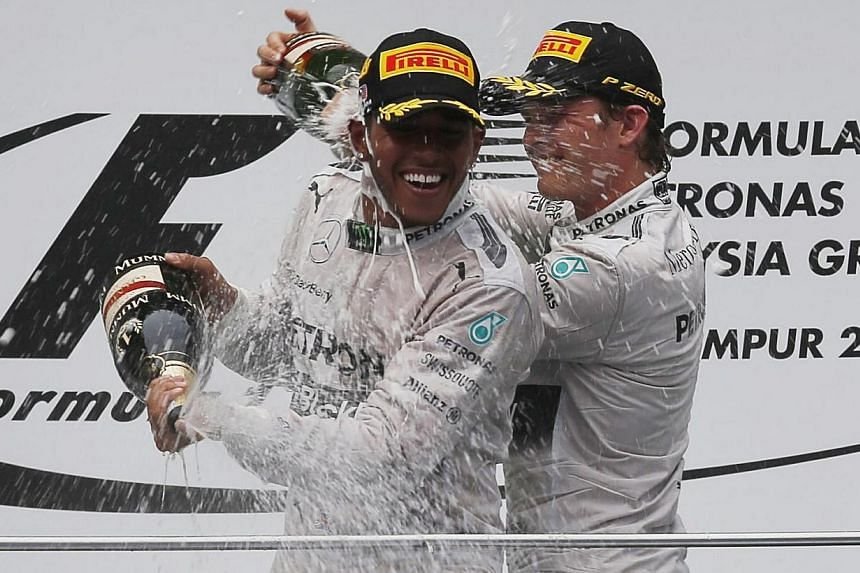 Mercedes Formula One driver Lewis Hamilton of Britain sprays champagne on the podium with team mate second-placed Nico Rosberg of Germany after winning the Malaysian F1 Grand Prix at Sepang International Circuit outside Kuala Lumpur, on March 30, 201